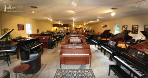 Front view to the back of Grafton Piano & Organ, showing pianos, organs and keyboards.